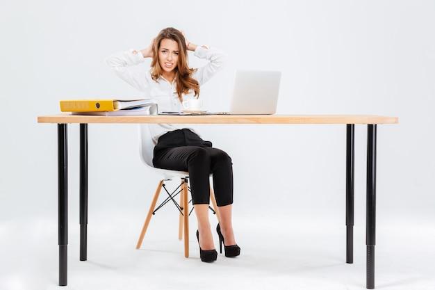Verwirrt verlegene junge geschäftsfrau, die mit laptop am tisch auf weißem hintergrund arbeitet