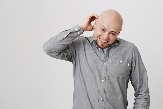 Verwirrt widerstrebender glatzkopf kratzt sich am kopf und verzieht das gesicht