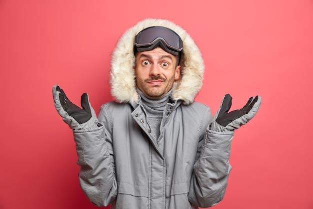 Verwirrt zögernder erwachsener europäischer mann zuckt zweifelnd mit den schultern, trägt winteroberbekleidung und handschuhe gehen im winter skifahren.