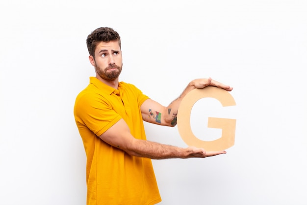 Verwirrt, zweifelhaft, denkend, den buchstaben g des alphabets haltend, um ein wort oder einen satz zu bilden.