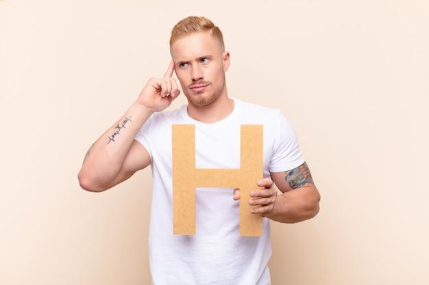 Verwirrt, zweifelhaft, denkend, den buchstaben h des alphabets haltend, um ein wort oder einen satz zu bilden.