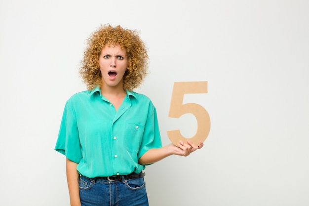 Verwirrt, zweifelhaft, denkend, nummer 5 in der hand.