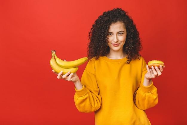 Verwirrt zwischen gesundem und ungesundem essen zu entscheiden, hält sie früchte und donut auf ihren händen, isoliert auf rotem hintergrund.