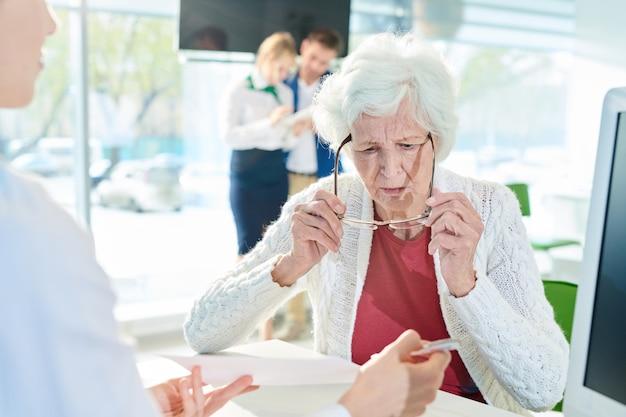 Verwirrte ältere dame, die dokument im bankbüro prüft