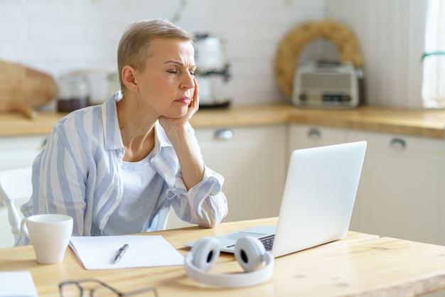 Verwirrte ältere frau, die den kopf in den händen hält und auf dem laptop schaut, während sie von zu hause aus online arbeitet