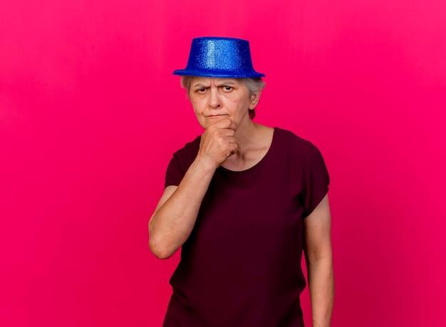 Verwirrte ältere frau, die partyhut trägt, legt hand auf kinn, das kamera auf rosa betrachtet