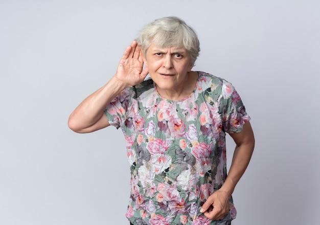 Verwirrte ältere frau hält hand hinter ohr, das versucht, isoliert auf weißer wand zu hören