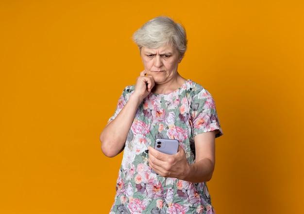 Verwirrte ältere frau legt hand auf kinn und betrachtet telefon lokalisiert auf orange wand