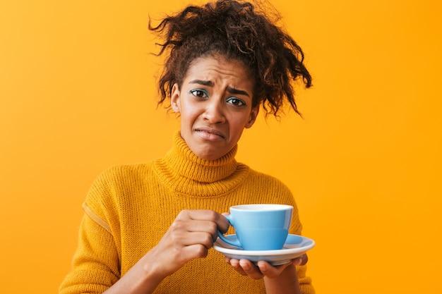 Verwirrte afrikanische frau, die pullover hält tasse auf untertasse isoliert