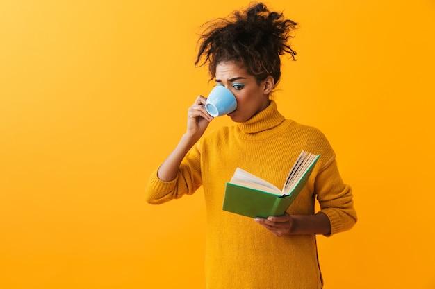 Verwirrte afrikanische frau, die pullover trägt, isoliert steht, ein buch liest, kaffee trinkt
