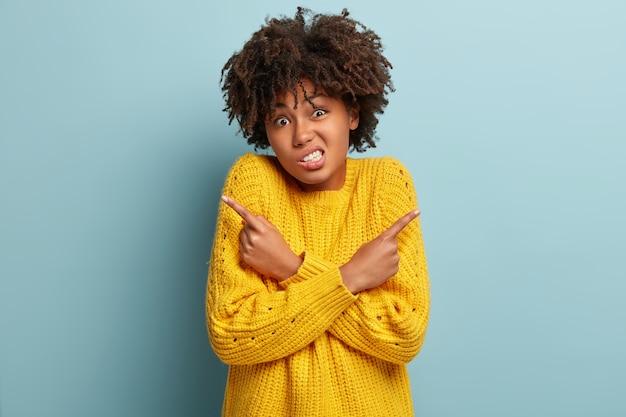 Verwirrte ahnungslose frau mit einem afro, der in einem rosa pullover posiert