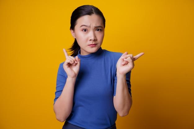 Verwirrte asiatische frau, die auf gelb denkt und steht.