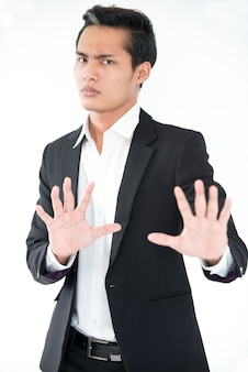 Verwirrte asiatische geschäftsmann zeigt stop geste