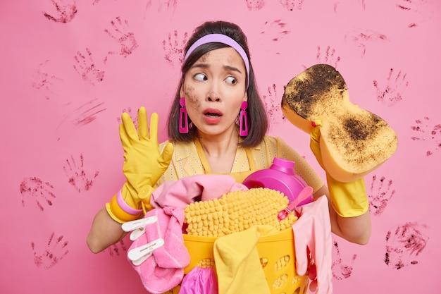 Verwirrte asiatische haushälterin versucht, ihr zuhause hell und sauber zu halten, schockiert, wie viel staub im zimmer ist, sieht auf schmutzigen schwamm, macht hausarbeiten in der nähe eines korbs voller wäsche verwendet reinigungsmittel