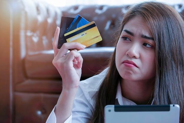 Verwirrte betonte asiatische frau, die in der hand zu viele kreditkarten betrachtet.