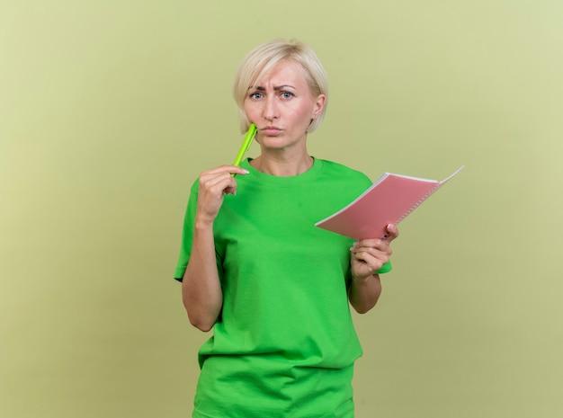 Verwirrte blonde frau mittleren alters, die notizblock hält, der die vordere berührende wange mit stift lokalisiert auf olivgrüner wand betrachtet