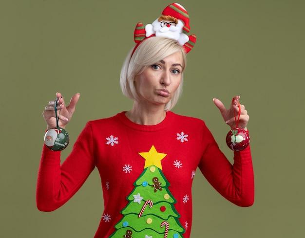 Verwirrte blonde frau mittleren alters, die weihnachtsmann-stirnband und weihnachtspullover hält, der weihnachtskugeln hält, die kamera lokalisiert auf olivgrünem hintergrund betrachten