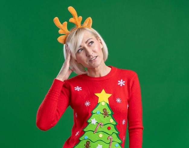 Verwirrte blonde frau mittleren alters, die weihnachtsrentiergeweih-stirnband und weihnachtspullover trägt, die seitenberührungskopf lokalisiert auf grünem hintergrund mit kopienraum betrachten