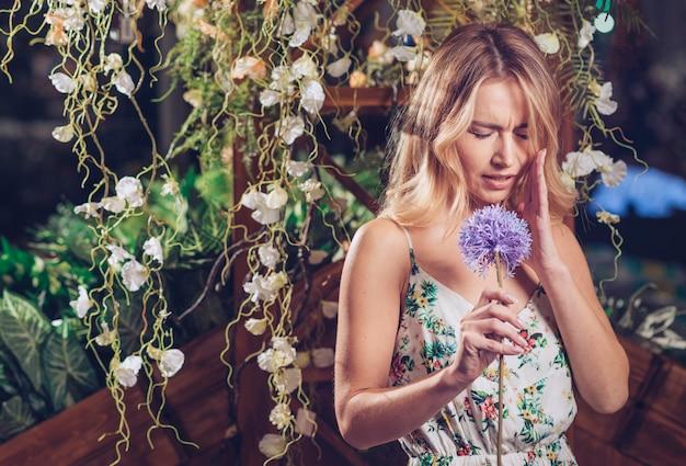Verwirrte blonde junge frau, die in der hand künstliche purpurrote lauchblume hält