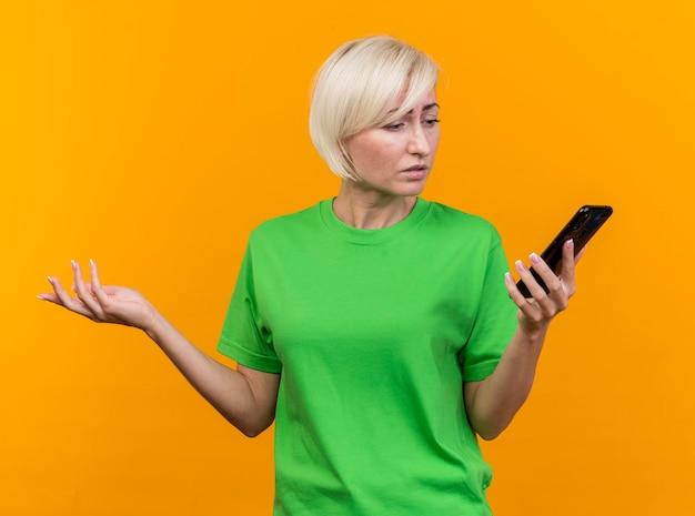 Verwirrte blonde slawische frau mittleren alters, die mobiltelefon lokalisiert auf gelbe wand hält und betrachtet