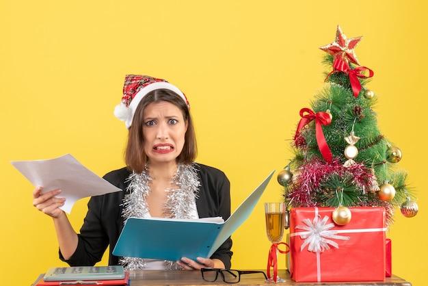 Verwirrte charmante dame im anzug mit weihnachtsmannhut und neujahrsdekorationen, die dokument im büro auf gelbem lokalisiert halten