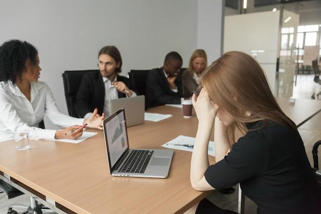 Verwirrte ernste geschäftsfrau besorgt über projektstatistiken bei der gruppensitzung