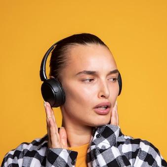 Verwirrte frau, die musik über kopfhörer hört