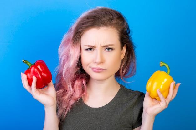 Verwirrte frau, die rote und gelbe paprika in verschiedenen händen hält