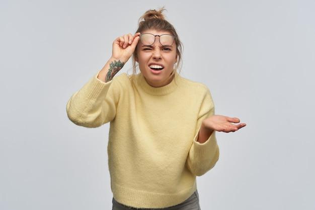 Verwirrte frau, getrenntes mädchen mit blonden haaren, die in brötchen und tätowierung gesammelt wurden. tragen eines gelben pullovers und einer brille. hebt ihre brille und zuckt die achseln. blick auf die kamera, isoliert über weiße wand