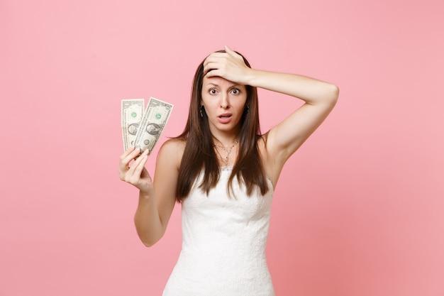 Verwirrte frau im weißen kleid, die hand auf der stirn hält und dollarnoten hält