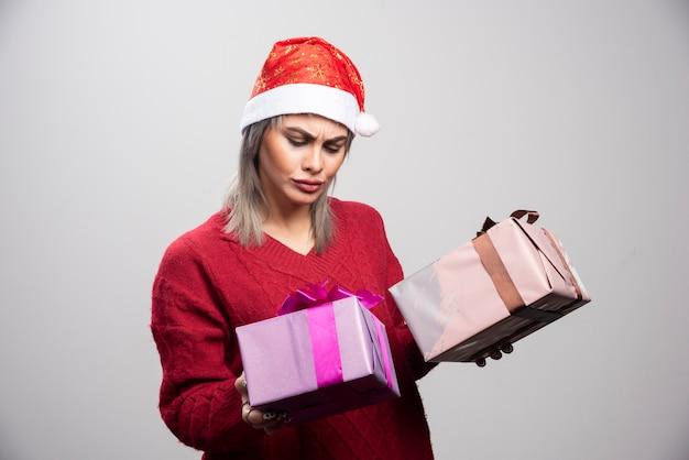 Verwirrte frau in sankt-hut, die weihnachtsgeschenke betrachtet.