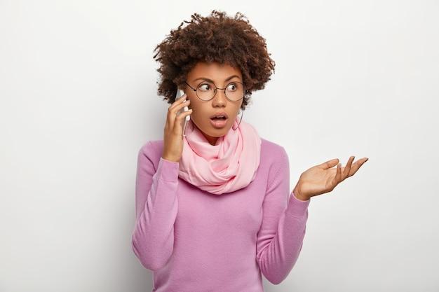 Verwirrte frau mit afro-frisur, unterhält sich mit kollegen oder freunden, versucht das problem per smartphone zu lösen, konzentriert sich beiseite, trägt eine optische brille, einen lila freizeitpullover und einen schal um den hals