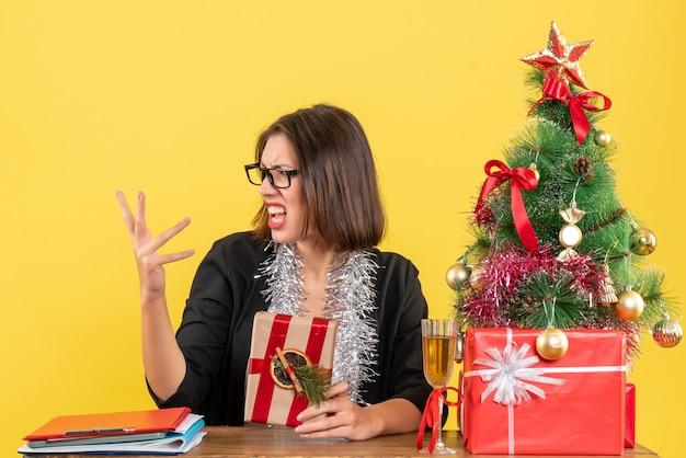 Verwirrte geschäftsdame im anzug mit brille, die ihr geschenk hält und an einem tisch mit einem weihnachtsbaum darauf im büro sitzt