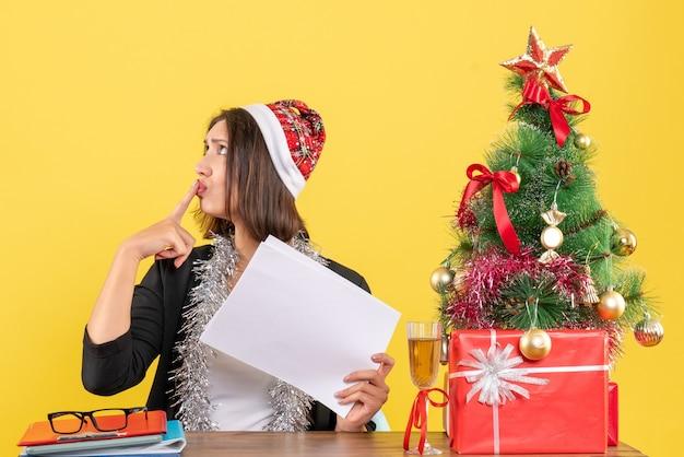 Verwirrte geschäftsdame im anzug mit weihnachtsmannhut und neujahrsdekorationen, die alleine arbeiten, dokumente halten und an einem tisch mit einem weihnachtsbaum darauf im büro sitzen