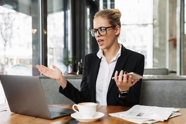 Verwirrte geschäftsfrau, die laptop-computer und telefon verwendet