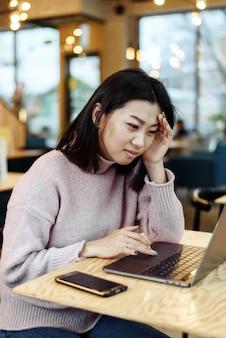 Verwirrte geschäftsfrau genervt durch online-problem, spam-e-mail oder gefälschte internetnachrichten, die laptop betrachten. arbeitnehmerin, die sich über einen festgefahrenen computer schockiert fühlt, verwirrt von betrugsnachrichten oder viren