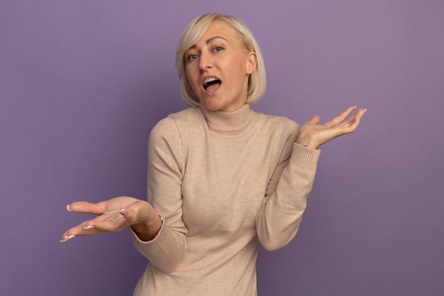 Verwirrte hübsche blonde slawische frau hält hände offen auf lila