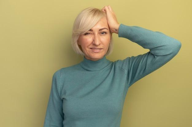 Verwirrte hübsche blonde slawische frau legt hand auf kopf auf olivgrün