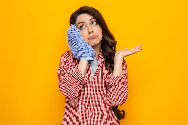 Verwirrte hübsche kaukasische putzfrau, die einen mikrofaser-reinigungshandschuh nahe am kopf hält und die hand offen hält