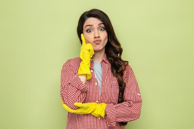 Verwirrte hübsche kaukasische putzfrau mit gummihandschuhen, die sich die hand aufs gesicht legt und schaut