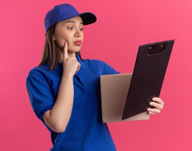 Verwirrte hübsche lieferfrau in uniform legt den finger auf das gesicht, das karton hält und die zwischenablage einzeln auf rosa wand mit kopienraum betrachtet