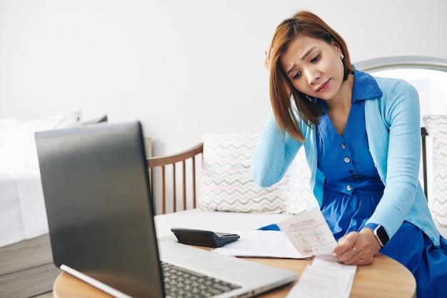 Verwirrte junge asiatische hausfrau, die rechnungen prüft und ausgaben zählt