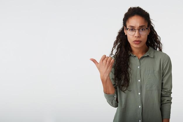 Verwirrte junge attraktive lockige brünette dame mit dunkler haut runzelte verwirrt die augenbrauen, während sie beiseite zeigte, isoliert über weißem hintergrund in freizeitkleidung