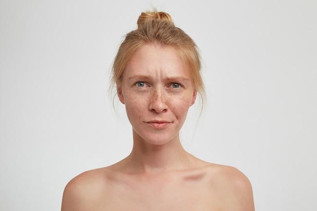 Verwirrte junge attraktive rothaarige frau, die ihr schickes haar im knoten trägt, während sie über der weißen wand posiert, die augenbrauen runzelt und dabei die lippen gefaltet hält