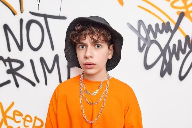 Verwirrte junge blicke unzufrieden in der kamera trägt hut orange t-shirt und ketten gehört zur jugend subkultur verbringt freizeit mit freunden des gleichen alters posen gegen graffiti-wand