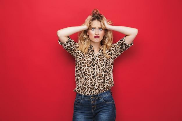 Verwirrte junge blonde frau, die make-up betrachtet kamera lokalisiert über rotem hintergrund
