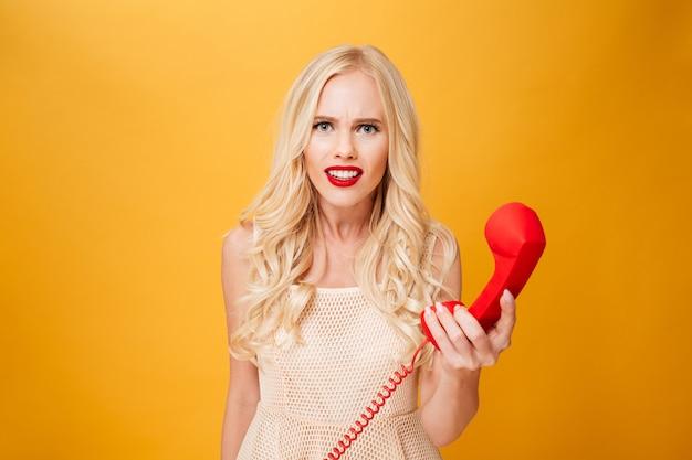 Verwirrte junge blonde frau, die telefon hält.
