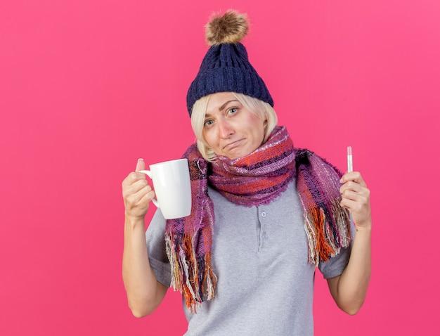 Verwirrte junge blonde kranke slawische frau, die wintermütze und schal trägt, hält tasse