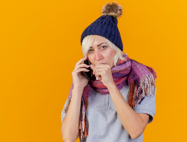 Verwirrte junge blonde kranke slawische frau, die wintermütze und schal trägt, spricht am telefon, das hand nahe am mund hält, lokalisiert auf orange wand mit kopienraum