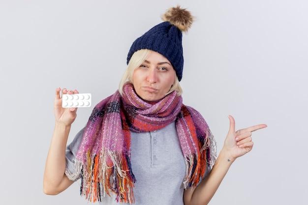 Verwirrte junge blonde kranke slawische frau, die wintermütze und schal trägt
